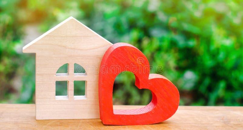 Σπίτι με μια κόκκινη ξύλινη καρδιά Σπίτι των εραστών Προσιτή κατοικία για τις νέες οικογένειες Σπίτι ημέρας βαλεντίνων ` s στοκ φωτογραφία με δικαίωμα ελεύθερης χρήσης