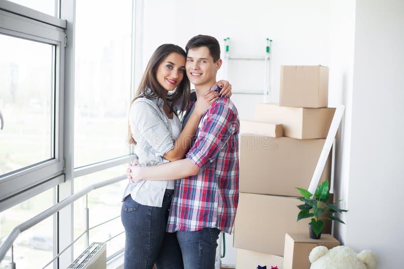 σπίτι νέο Το αστείο νέο ζεύγος απολαμβάνουν και η κίνηση εορτασμού προς το νέο σπίτι Ευτυχές ζεύγος στο κενό δωμάτιο του νέου σπι στοκ φωτογραφία