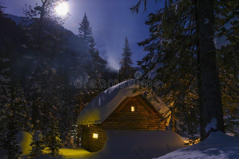 Σπίτι νεράιδων, ο καπνός από την καπνοδόχο, φεγγαρόφωτη χειμερινή νύχτα στοκ εικόνα με δικαίωμα ελεύθερης χρήσης