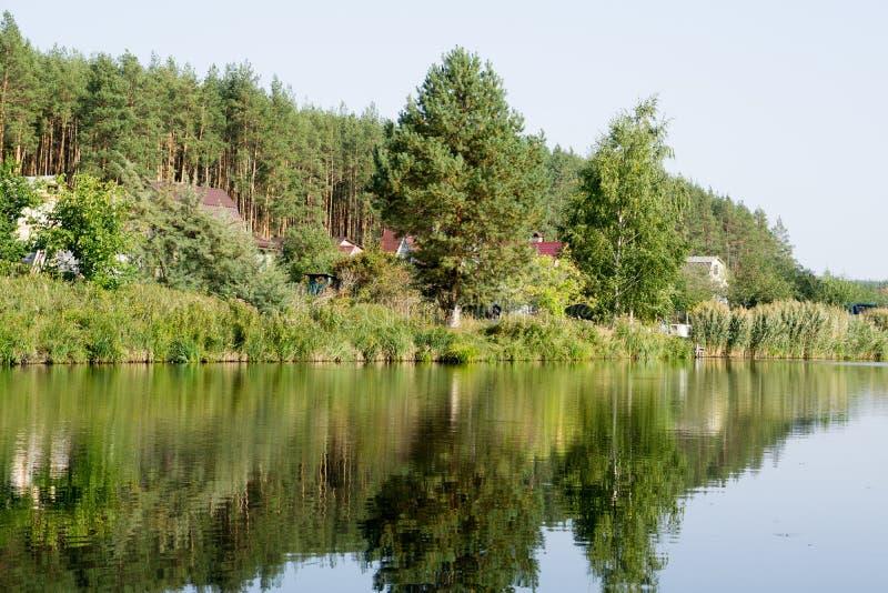 Σπίτι ποταμών με τις αντανακλάσεις και το μπλε ουρανό στοκ φωτογραφία
