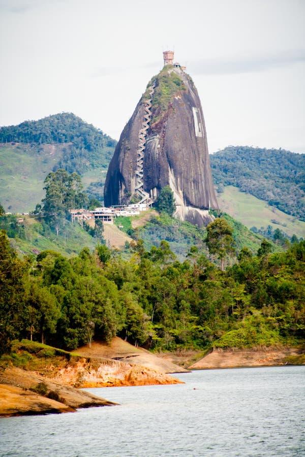 Σπίτι πύργων πέρα από ένα μεγάλο βουνό βράχου Peñon Guatape στοκ εικόνα