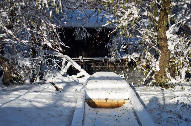 Σπίτι σε ένα σύνολο και μια μικρή βάρκα που καλύπτονται με το χιόνι στοκ εικόνες