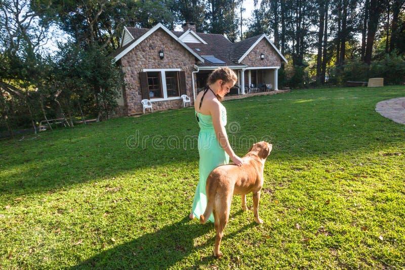 Σπίτι σκυλιών περπατήματος κοριτσιών στοκ εικόνα με δικαίωμα ελεύθερης χρήσης