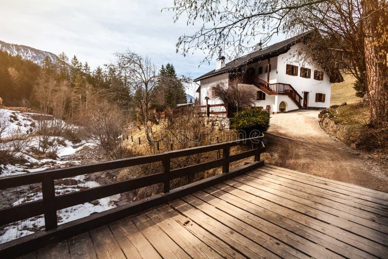 Σπίτι στα βουνά, το χιόνι και την ξύλινη γέφυρα άνετη κορυφή βουνών καλυ&b στοκ φωτογραφία