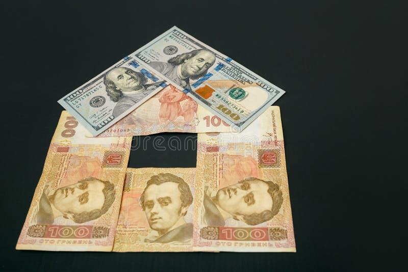 Σπίτι των λογαριασμών Το σπίτι έχει μια στέγη των λογαριασμών δολαρίων Οι λογαριασμοί είναι σε έναν σκοτεινό πίνακα στοκ φωτογραφίες
