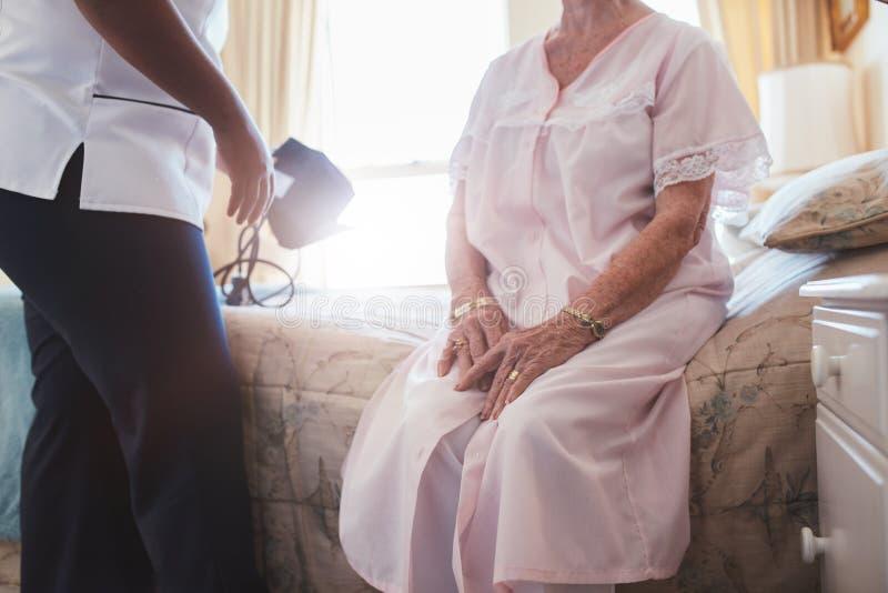 Σπίτι caregiver με την ανώτερη συνεδρίαση γυναικών στο κρεβάτι στοκ φωτογραφίες με δικαίωμα ελεύθερης χρήσης
