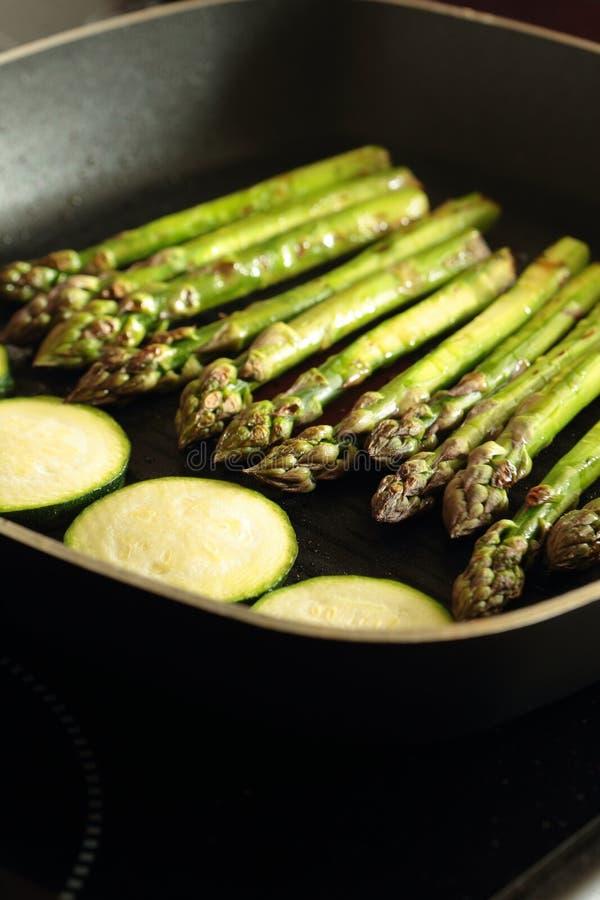 Σπαράγγι και τεμαχισμένα κολοκύθια κολοκυθιών που μαγειρεύουν σε ένα ταψάκι το τηγανίζοντας τηγάνι στοκ εικόνα με δικαίωμα ελεύθερης χρήσης
