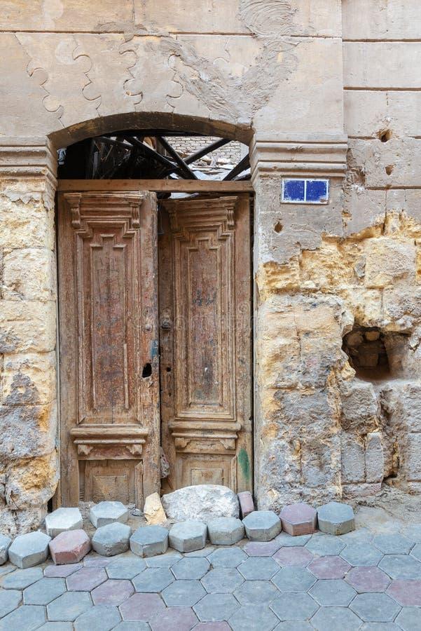 Σπασμένη ξύλινη πόρτα στον τοίχο τούβλων πετρών grunge στην εγκαταλειμμένη οδό στοκ φωτογραφία με δικαίωμα ελεύθερης χρήσης