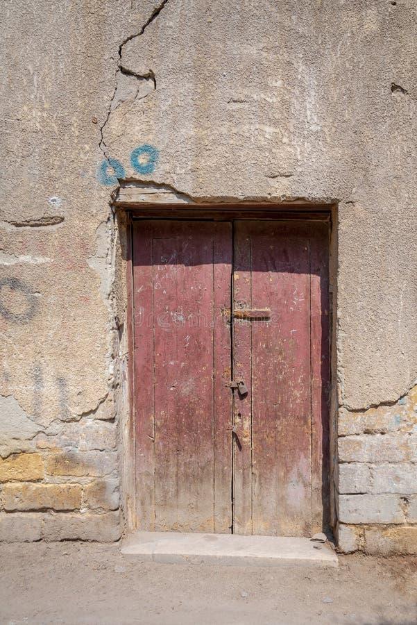 Σπασμένη ξύλινη πόρτα στον τοίχο τούβλων πετρών grunge στην εγκαταλειμμένη οδό στοκ εικόνες