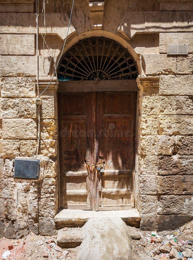 Σπασμένη ξύλινη πόρτα στον τοίχο τούβλων πετρών grunge στην εγκαταλειμμένη περιοχή στοκ εικόνες
