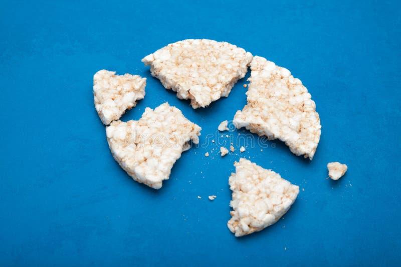 Σπασμένη φραντζόλα ρυζιού σε ένα μπλε υπόβαθρο στοκ εικόνα με δικαίωμα ελεύθερης χρήσης