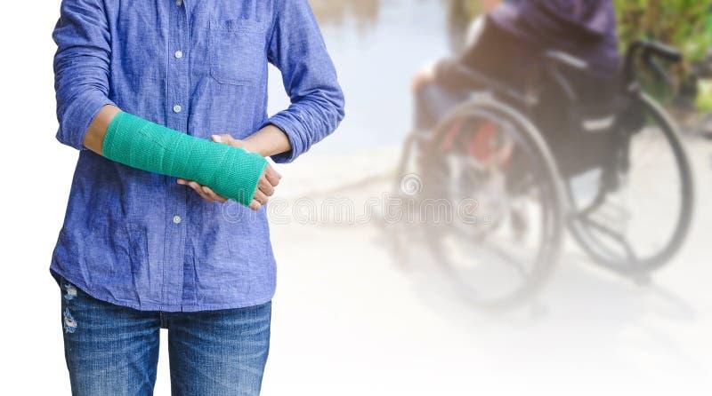 σπασμένος βραχίονας, γυναίκα τραυματισμών που στέκεται φορώντας το πουκάμισο και τα τζιν με το γ στοκ εικόνα