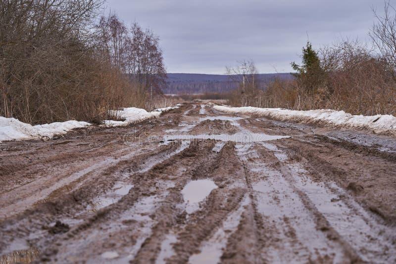 Σπασμένος βρώμικος δρόμος με τις λακκούβες την πρώιμη άνοιξη στοκ φωτογραφίες με δικαίωμα ελεύθερης χρήσης