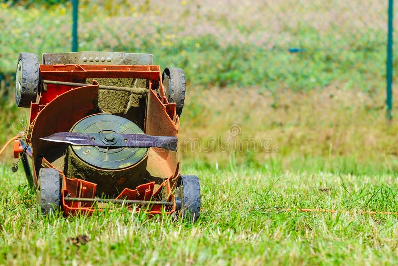 Σπασμένος παλαιός χορτοκόπτης στη χλόη κατωφλιών στοκ εικόνες με δικαίωμα ελεύθερης χρήσης