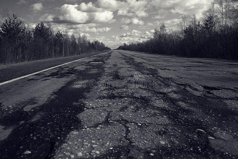 Σπασμένος δρόμος με τις τρύπες στοκ εικόνες με δικαίωμα ελεύθερης χρήσης