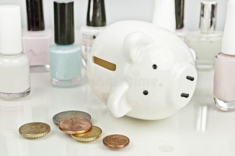 Σπασμένος στα καλλυντικά - piggy τράπεζα, νομίσματα, στιλβωτική ουσία καρφιών στοκ εικόνες