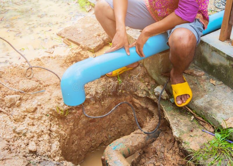 Σπασμένος σωλήνας στην τρύπα με την κίνηση νερού στην επισκευή εργασίας ακρών του δρόμου και υδραυλικών στοκ εικόνες με δικαίωμα ελεύθερης χρήσης