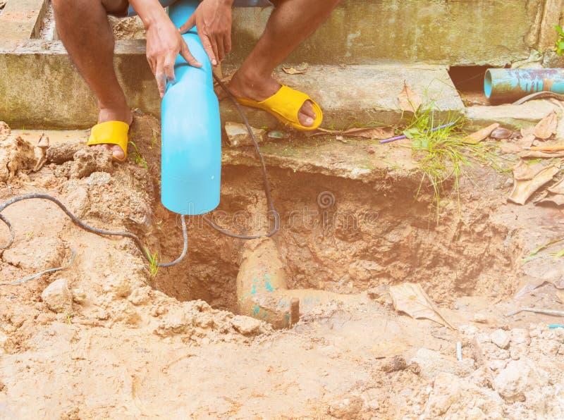 Σπασμένος σωλήνας στην τρύπα με την κίνηση νερού στην επισκευή εργασίας ακρών του δρόμου και υδραυλικών στοκ φωτογραφία
