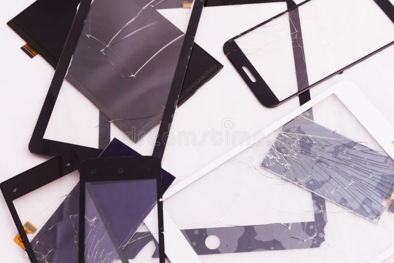 Σπασμένος σωρός οθονών επαφής που βρίσκεται γύρω από ένα διαφορετικό μέγεθος σε ένα άσπρο υπόβαθρο Στα γυαλιά είναι ραγισμένος απ στοκ φωτογραφίες