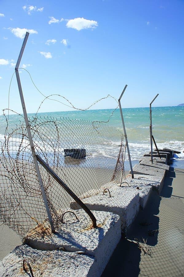 Σπασμένος φράκτης πλέγματος καλωδίων σε μια παραλία στοκ φωτογραφίες