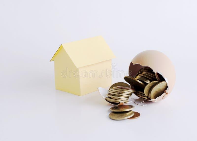 Σπασμένο αυγό με τα νομίσματα μέσα και το έγγραφο σπιτιών για την έννοια χρημάτων στεγαστικών δανείων στοκ φωτογραφία με δικαίωμα ελεύθερης χρήσης