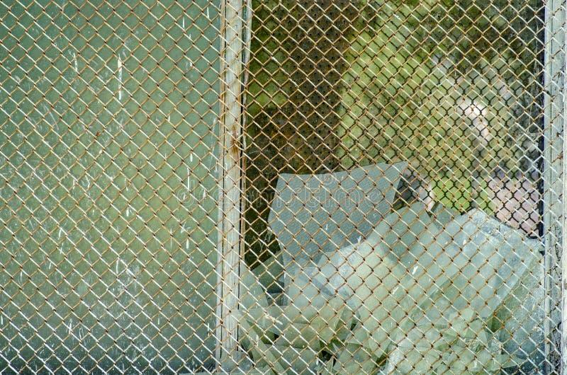 Σπασμένο γυαλί πίσω από το πλέγμα στοκ εικόνα με δικαίωμα ελεύθερης χρήσης