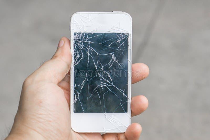 Σπασμένο εκμετάλλευση κινητό τηλέφωνο χεριών στοκ φωτογραφία