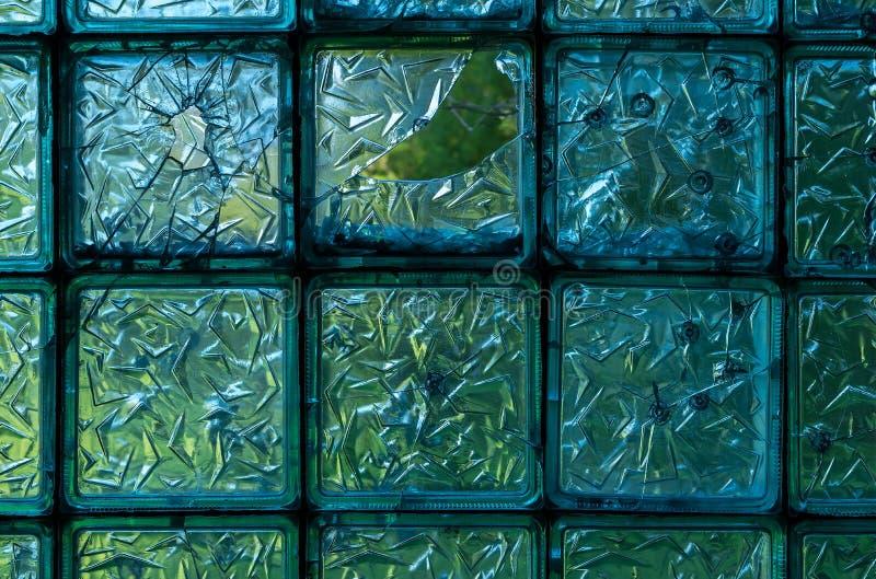 Σπασμένο ζαρωμένο γυαλί ενός παλαιού εγκαταλειμμένου κτηρίου με τα ίχνη τρυπών από σφαίρα στοκ εικόνες