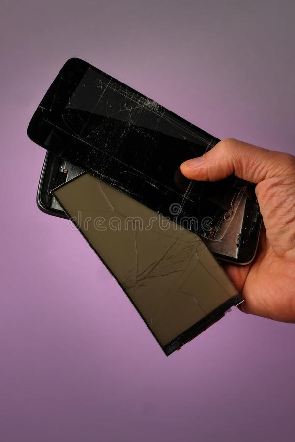Σπασμένο μαύρο κινητό smartphone με μια ραγισμένη επίδειξη που βρίσκεται στο χέρι του, σε ένα ιώδες υπόβαθρο, την μπροστινή άποψη στοκ φωτογραφίες