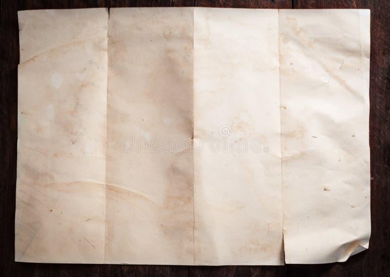Σπασμένο τρύγος κενό διπλωμένο και τσαλακωμένο έγγραφο για το σκοτεινό ξύλινο πίνακα στοκ φωτογραφία