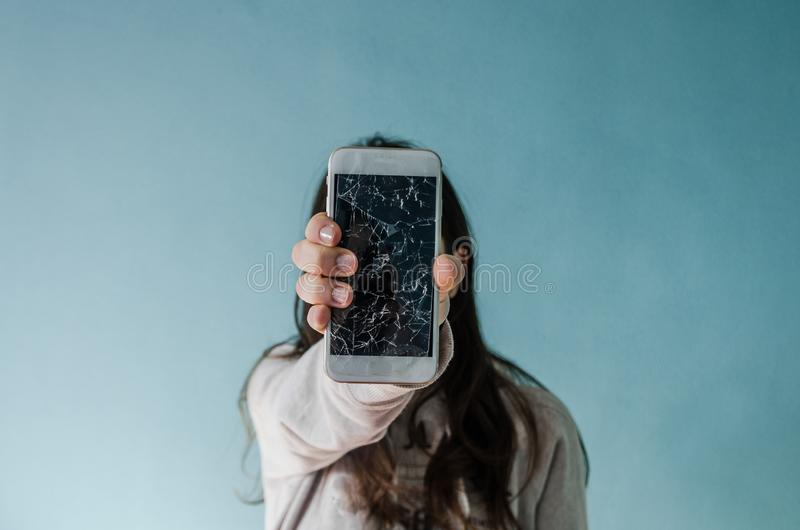 Σπασμένο smartphone οθόνης γυαλιού υπό εξέταση της γυναίκας στοκ εικόνες
