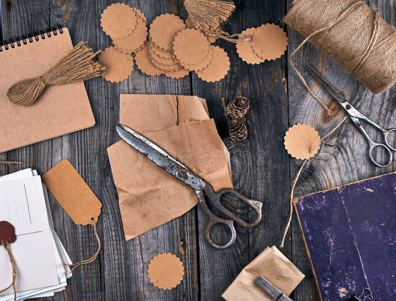 σπείρα του καφετιού σχοινιού, των ετικεττών εγγράφου και του παλαιού ψαλιδιού σε ένα γκρίζο ξύλινο υπόβαθρο στοκ φωτογραφία με δικαίωμα ελεύθερης χρήσης