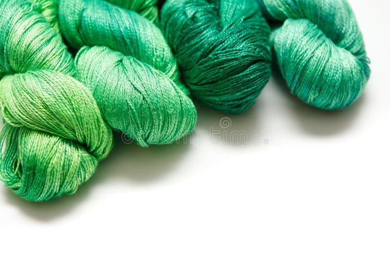 Σπείρες του πράσινου νήματος στο άσπρο υπόβαθρο στοκ εικόνες