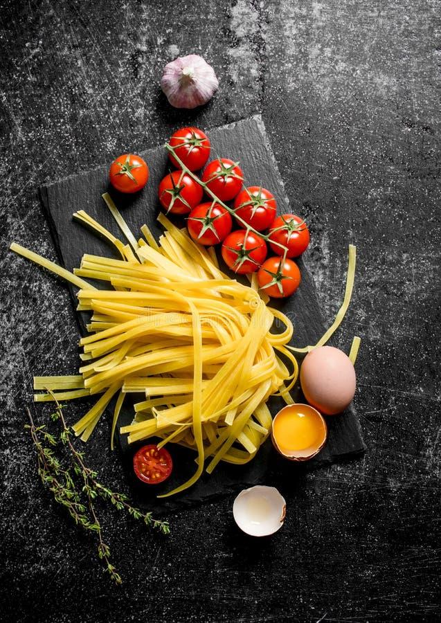 Σπιτικά ακατέργαστα ζυμαρικά με τα αυγά, τις ντομάτες και το σκόρδο σε έναν πίνακα πετρών στοκ εικόνα
