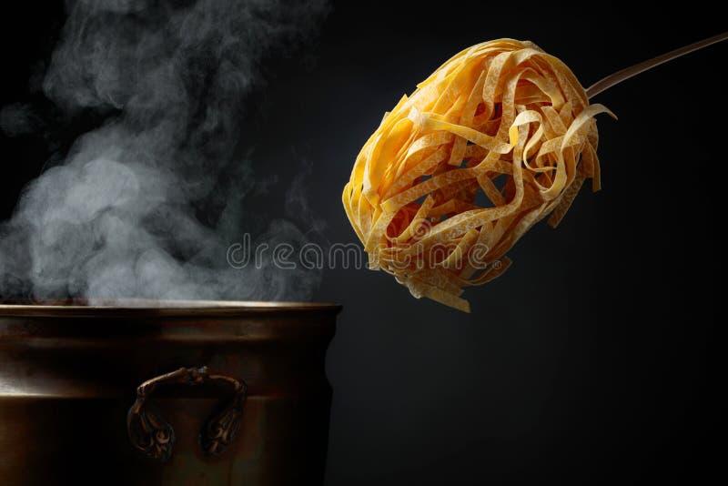 Σπιτικά ακατέργαστα νουντλς αυγών και παλαιό τηγάνι ορείχαλκου με το ζεστό νερό στοκ εικόνες