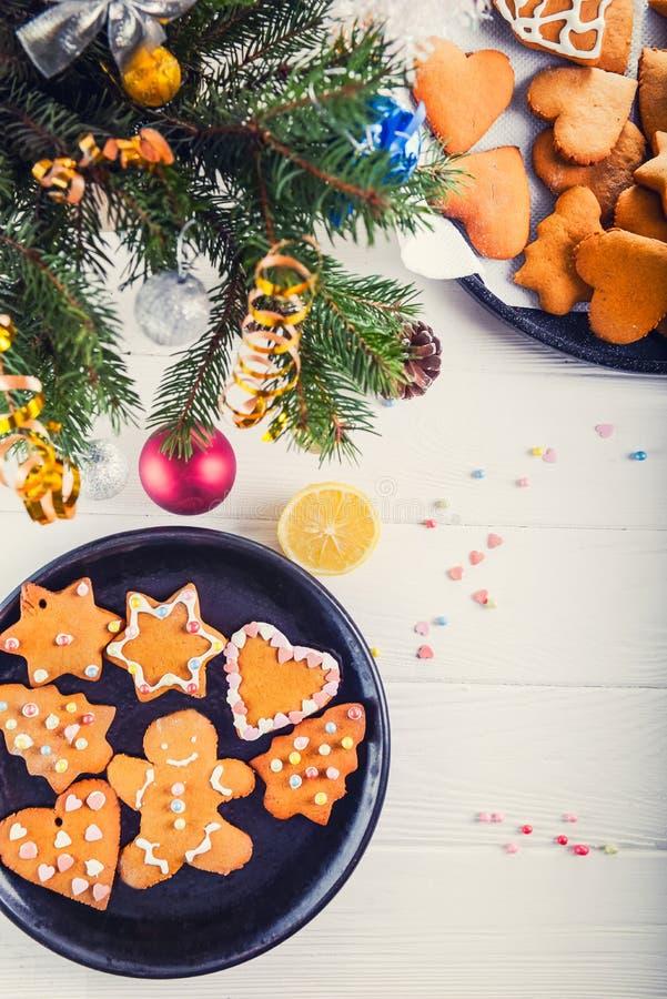 Σπιτικά μπισκότα μελοψωμάτων Χριστουγέννων στον άσπρο ξύλινο πίνακα, έννοια υποβάθρου Χριστουγέννων Η διαδικασία με το mer στοκ εικόνες με δικαίωμα ελεύθερης χρήσης