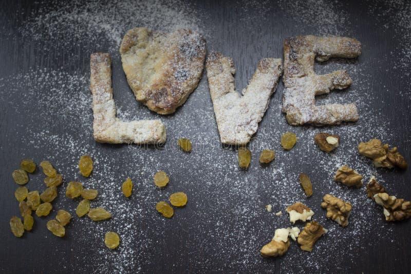 Σπιτικά μπισκότα με τα καρύδια και σταφίδα που ψεκάζεται με το αλεύρι στοκ εικόνες