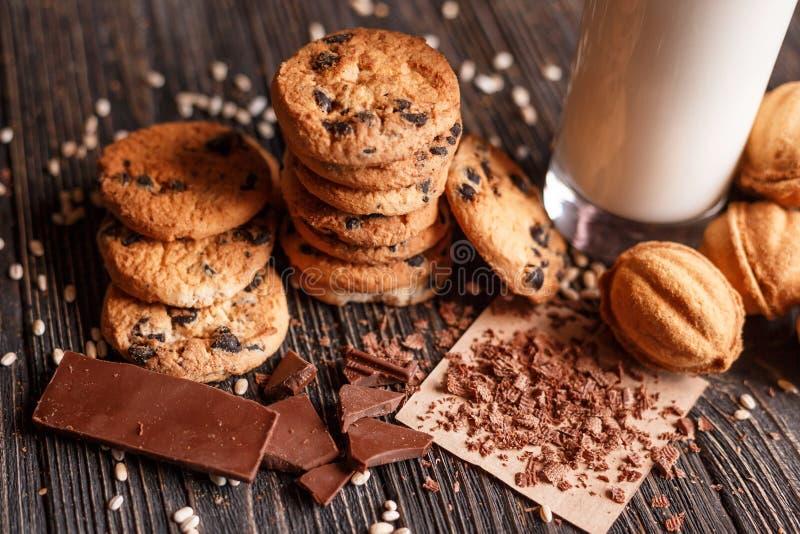 Σπιτικά μπισκότα τσιπ σοκολάτας και μπισκότα με το γλυκό με το ποτήρι του γάλακτος στοκ φωτογραφίες