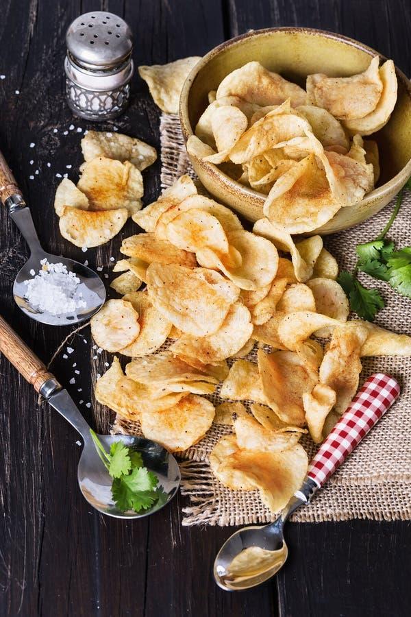 Σπιτικά τσιπ πατατών πέρα από το σκοτεινό ξύλινο υπόβαθρο στοκ φωτογραφία