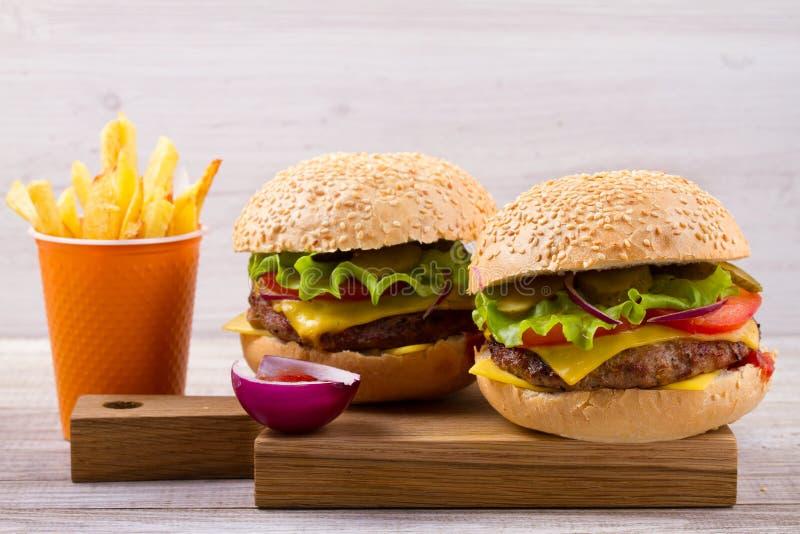 Σπιτικά burgers και τηγανητά στο ξύλινο υπόβαθρο στοκ φωτογραφία με δικαίωμα ελεύθερης χρήσης