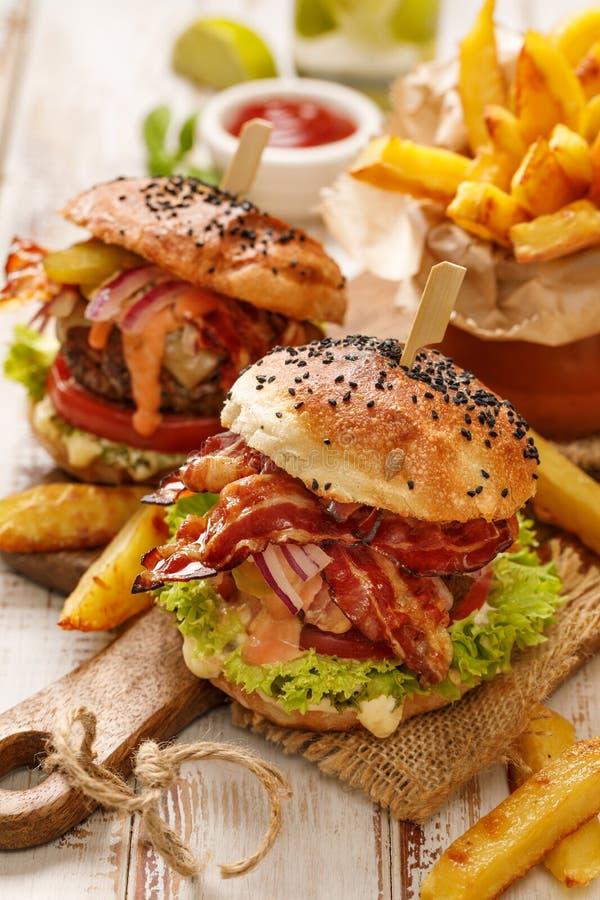 Σπιτικά burgers με το ψημένο στη σχάρα μπέϊκον, το κόκκινο κρεμμύδι, το φρέσκο μαρούλι, τα τουρσιά αγγουριών, την ντομάτα και την στοκ εικόνες