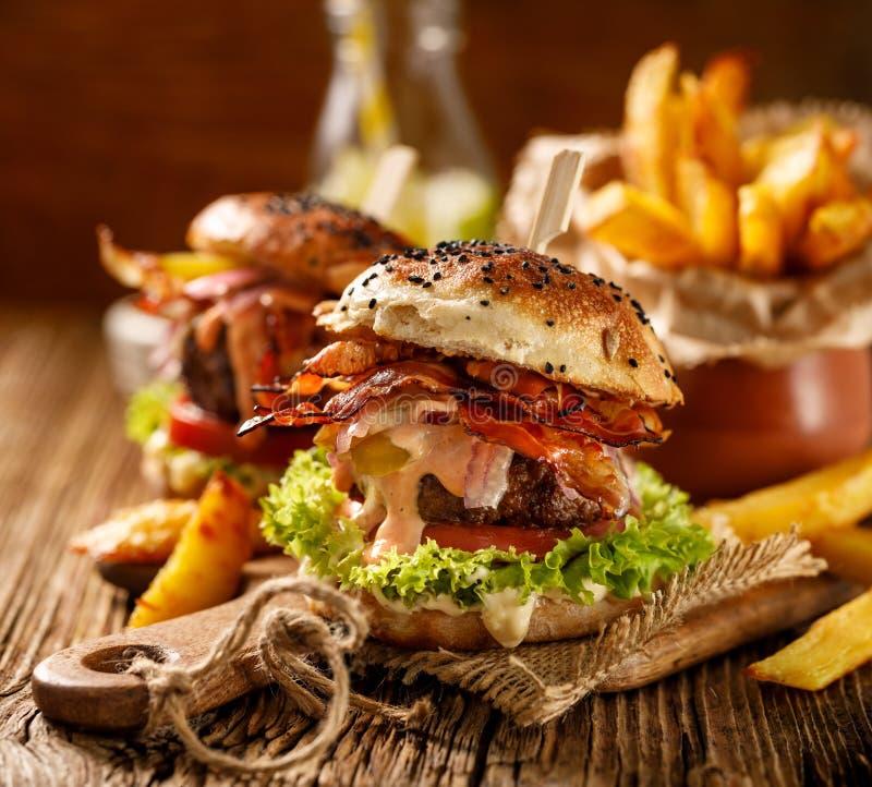 Σπιτικά burgers με το ψημένο στη σχάρα μπέϊκον, το κόκκινο κρεμμύδι, το φρέσκο μαρούλι, τα τουρσιά αγγουριών, την ντομάτα και την στοκ εικόνα