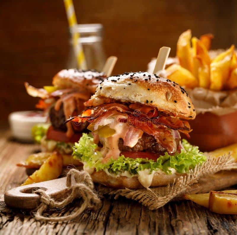 Σπιτικά burgers με το ψημένο στη σχάρα μπέϊκον, το κόκκινο κρεμμύδι, το φρέσκο μαρούλι, τα τουρσιά αγγουριών, την ντομάτα και την στοκ φωτογραφία