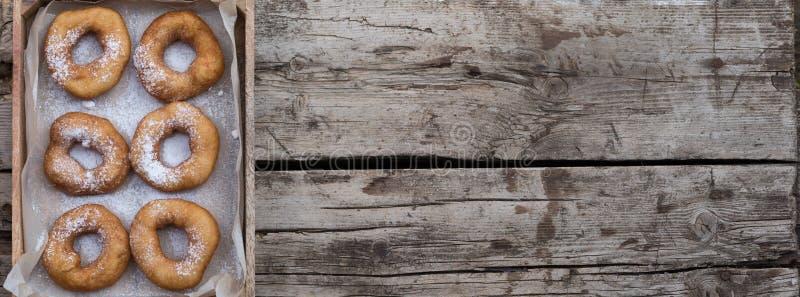 Σπιτικά donuts με τη σκόνη ζάχαρης τήξης στο ξύλινο υπόβαθρο στοκ φωτογραφία με δικαίωμα ελεύθερης χρήσης