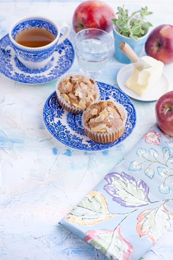Σπιτικά muffins με τα αμύγδαλα σε ένα μπλε πιάτο για το πρόγευμα και το τσάι σε ένα φλυτζάνι Ένα ποτήρι του νερού και ενός κόκκιν στοκ εικόνες