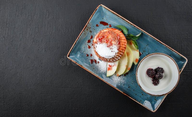 Σπιτικά muffins με το γιαούρτι, το βακκίνιο, το μήλο και τη μαρμελάδα στο πιάτο στο σκοτεινό υπόβαθρο πετρών Υγιές πρόγευμα στοκ εικόνες με δικαίωμα ελεύθερης χρήσης