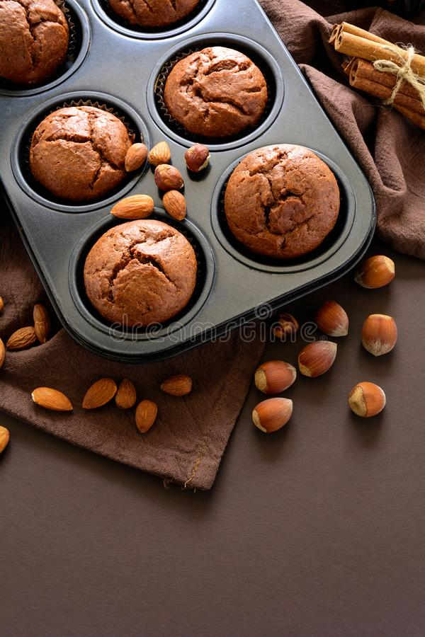 Σπιτικά muffins σοκολάτας brownies με την κανέλα, τα αμύγδαλα και τα φουντούκια στο υπόβαθρο καφετιού εγγράφου στοκ εικόνες με δικαίωμα ελεύθερης χρήσης