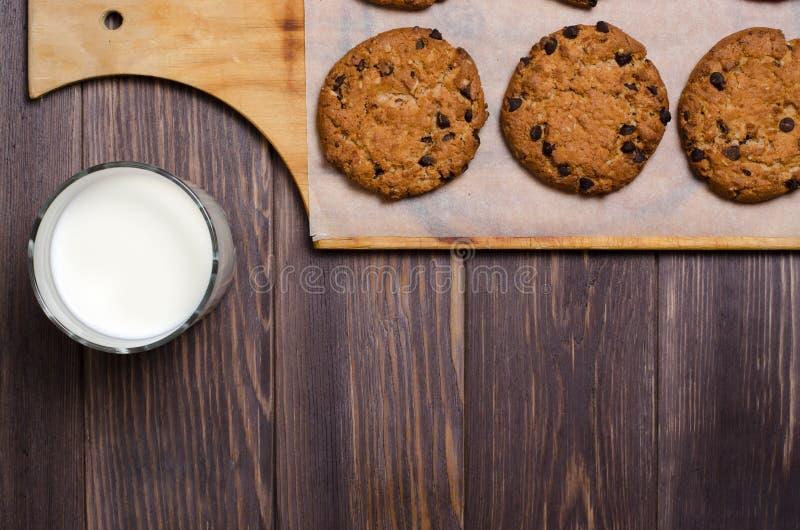Σπιτικά oatmeal μπισκότα σε έναν ξύλινους τέμνοντες πίνακα και ένα γάλα Επιζητήστε στοκ φωτογραφία με δικαίωμα ελεύθερης χρήσης