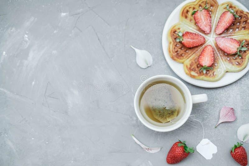 Σπιτικές βελγικές βάφλες με τις φράουλες και βοτανικό τσάι σε ένα γ στοκ φωτογραφία με δικαίωμα ελεύθερης χρήσης