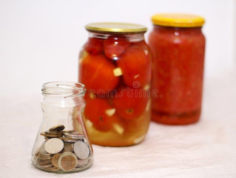 Σπιτικές παστωμένες ντομάτες στο βάζο και τα χρήματα στοκ φωτογραφία